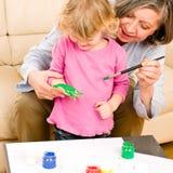 Liten flicka med handprints för farmorspelrummålarfärg arkivbild
