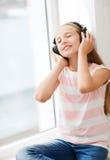 Liten flicka med hemmastadd hörlurar Arkivbild