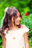 Liten flicka med henne första nattvardsgångklänning Arkivbilder