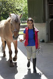 Liten flicka med henne favorit- häst arkivfoton