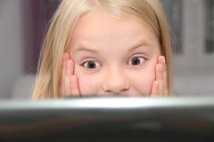 Liten flicka med hennes dator som är hemmastadd på tabellen Royaltyfria Bilder