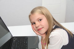 Liten flicka med hennes dator som är hemmastadd på tabellen Royaltyfri Bild