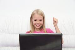Liten flicka med hennes dator som är hemmastadd på tabellen Arkivfoto