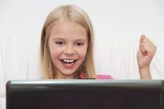 Liten flicka med hennes dator som är hemmastadd på tabellen Royaltyfri Foto
