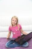 Liten flicka med hennes dator som är hemmastadd på tabellen Royaltyfria Foton