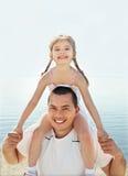 Liten flicka med hennes fader som har gyckel på strandsemester Arkivbilder
