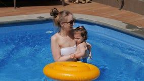 Liten flicka med hennes mamma med den uppblåsbara cirkeln i simbassäng stock video