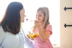 Liten flicka med hennes moder i köket som äter en ny frukt royaltyfri foto