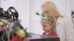 Liten flicka med hennes moder som spelar pianot Flygel som dekoreras med nytt års dekor stock video