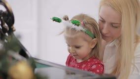 Liten flicka med hennes moder som spelar pianot Flygel som dekoreras med nytt års dekor arkivfilmer