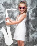 Liten flicka med hennes saxofon Arkivbild