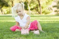 Liten flicka med hennes spargrisar utanför Arkivbild