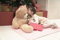 Liten flicka med hennes vän för nallebjörn på julafton Arkivfoto