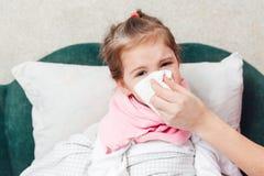 Liten flicka med influensa som blåser näsan Fotografering för Bildbyråer