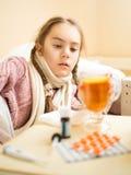 Liten flicka med influensa som ligger i säng och ser kopp te fotografering för bildbyråer