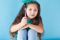 Liten flicka med inga tänder med en tandborste i tandläkekonst arkivfoton