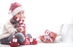 Liten flicka med julgåvan i jultomtendräkt arkivbild