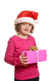 Liten flicka med julgåvan och den santa hatten Fotografering för Bildbyråer