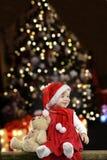 Liten flicka med julhatten och nallebjörnen på svart Royaltyfri Bild