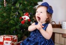Liten flicka med klubban och julgran och garnering Arkivfoton