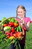 liten flicka med korgen av grönsaker Arkivbilder