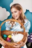 Liten flicka med korgen med färgägg och den vita påskkaninen Royaltyfri Bild