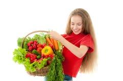liten flicka med korggrönsaker arkivfoton
