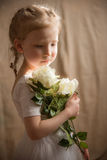 Liten flicka med krämiga rosor Royaltyfri Fotografi