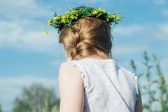 Liten flicka med kransen av vildblommor på hennes huvud Royaltyfria Bilder