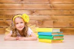 Liten flicka med kransen som ligger nära bunt av böcker royaltyfria foton