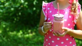 Liten flicka med kruset av yoghurt i trädgården bland hallonbuskarna, closeup Autentisk livsstilbild Säsongsbetonad skördskörd royaltyfria bilder