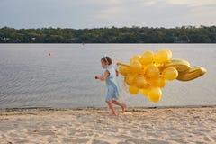 Liten flicka med många guld- ballonger på stranden på solnedgången Royaltyfria Foton
