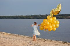 Liten flicka med många guld- ballonger på stranden på solnedgången Royaltyfri Bild