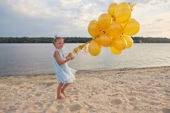 Liten flicka med många guld- ballonger på stranden på solnedgången Royaltyfri Fotografi