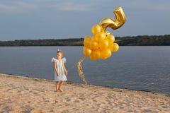 Liten flicka med många guld- ballonger på stranden på solnedgången Arkivfoton
