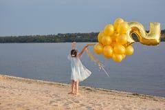 Liten flicka med många guld- ballonger på stranden på solnedgången Fotografering för Bildbyråer