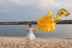 Liten flicka med många guld- ballonger på stranden på solnedgången Arkivbild