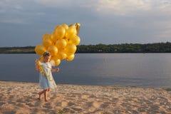 Liten flicka med många guld- ballonger på stranden på solnedgången Royaltyfri Foto