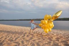 Liten flicka med många guld- ballonger på stranden på solnedgången Arkivfoto