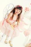 Liten flicka med mjukt leksaksammanträde på en stol. Royaltyfria Bilder