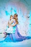 Liten flicka med modern i prinsessaklänning på en bakgrund av en w royaltyfri foto