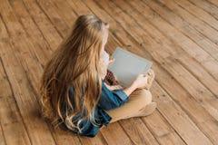 Liten flicka med nallebjörnen som använder den digitala minnestavlan Arkivbild