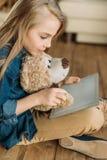 Liten flicka med nallebjörnen som använder den digitala minnestavlan Arkivbilder