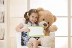 Liten flicka med nallebjörnen som håller ögonen på hennes minnestavladator Arkivfoton