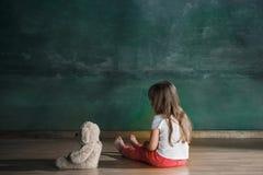Liten flicka med nallebjörnen som sitter på golv i tomt rum Autismbegrepp royaltyfri foto