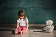 Liten flicka med nallebjörnen som sitter på golv i tomt rum Autismbegrepp arkivfoton