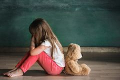 Liten flicka med nallebjörnen som sitter på golv i tomt rum Autismbegrepp royaltyfri fotografi