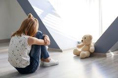 Liten flicka med nallebjörnen som sitter på golv nära fönster royaltyfri fotografi