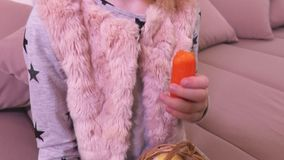 Liten flicka med påskägg i korg och morot på soffan