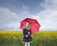 Liten flicka med paraplyet som är främre av en oilseed, sätter in Royaltyfri Foto